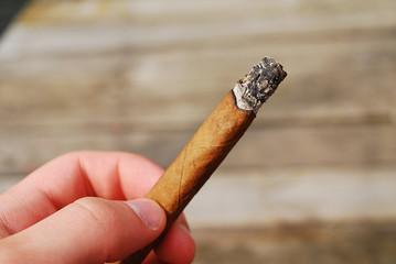 palenie cygara, cygaro w ręce - w tle deski, drewno