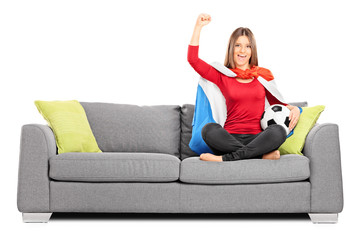 Female football fan cheering seated on a couch