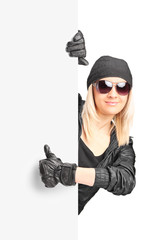 Female biker giving thumb up behind a panel