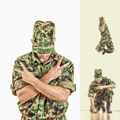 soldier with hidden face in green camouflage uniform jumping and