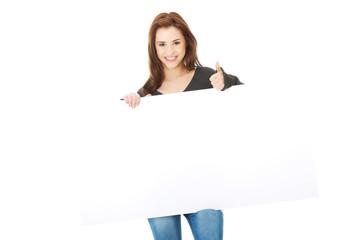 Portrait of happy woman with blank board