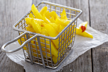 Homemade french fries in a frying basket