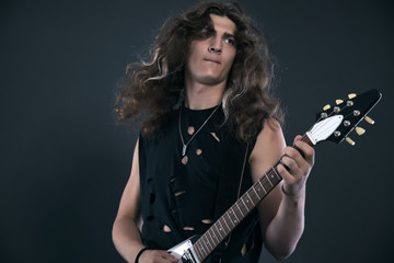 Male hard rock electric guitar musician with long hair. Studio s