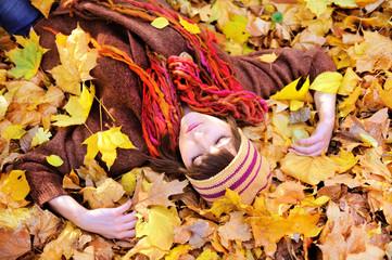 Girl lying in autumn leaves portrait.
