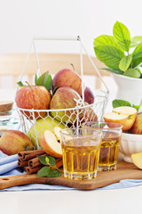 Apple juice and fresh apples on the table