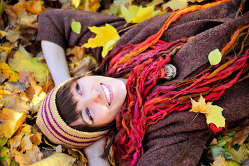Happy girl in knitted hat lying in autumn leaves.