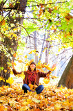 Woman throws autumn leaves in park.
