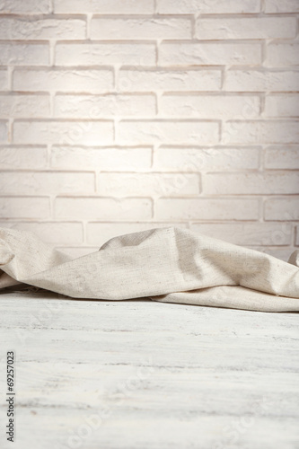Wooden table with cloth on wall background - 69257023