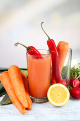 Glass of fresh carrot juice with vegetables on wooden table