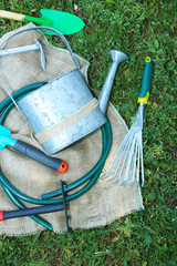Garden tools on green grass background