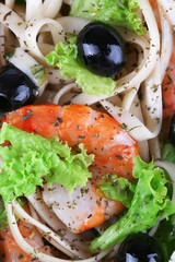 Fresh prawns with spaghetti, olives and lettuce closeup