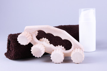 Wooden roller brush, towels and spray on grey background