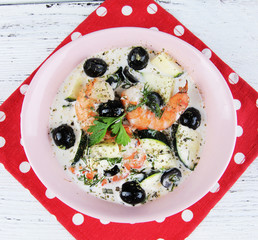 Fresh prawns with olives, avocado and parsley in white sauce in