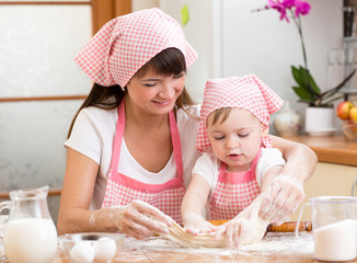 Mother and kid girl bake cookies together at kitchen