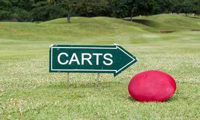 The golf carts sign on a golf field, for the direction