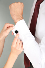 Woman helping man to do collar button up on grey background