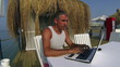 Man Using Laptop Computer by the Sea