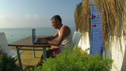 Man With Laptop Computer by the Ocean