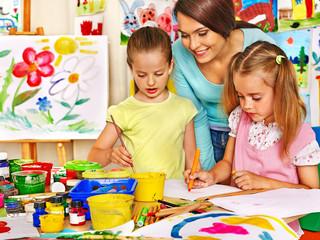 Children with teacher painting.
