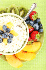 Cottage cheese with fruits and berries in bowl on table