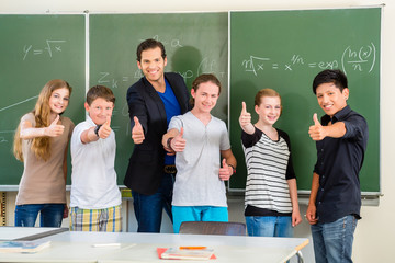 Lehrer mit Schülern in Schule vor Tafel