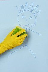 Hand in glove wiping children drawing on wallpaper