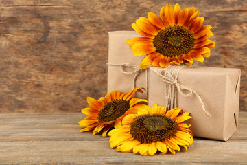 Sunflowers with present boxes on wooden background