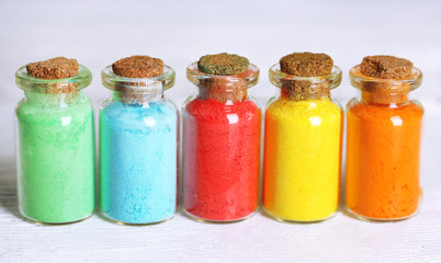 Bottles with colorful dry pigments on wooden background