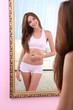 Beautiful woman with slim body posing near mirror in room