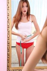 Beautiful woman with measuring tape posing near mirror in room