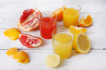Different sliced citrus fruits and glasses of juice