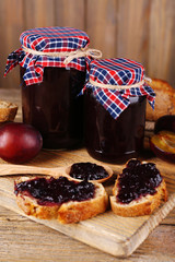 Tasty plum jam in jars and plums on wooden table