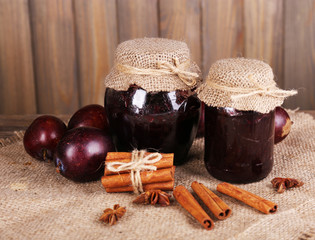 Tasty plum jam in jars and plums
