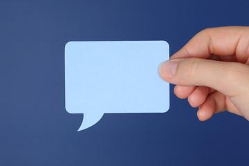 Hand holds speech bubble