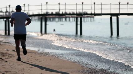 Mature Man Jogging On Sandy Beach
