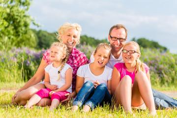 Familie sitzt im Grass auf Feld oder Wiese