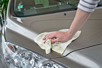 Hand of a man polishing a car with a wiper