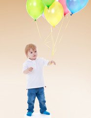 Little boy launches balloons.