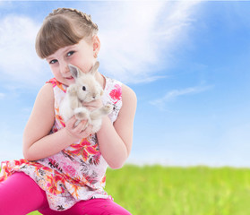 Little girl holding a rabbit sitting on meadow.