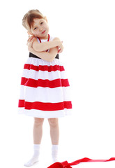 Girl in a striped dress hugging her arms
