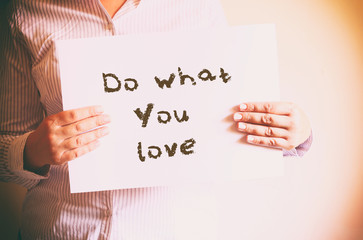 "woman holding board with the phrase ""do what you love"" written o"