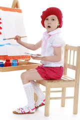 Girl in a red beret sits at an easel