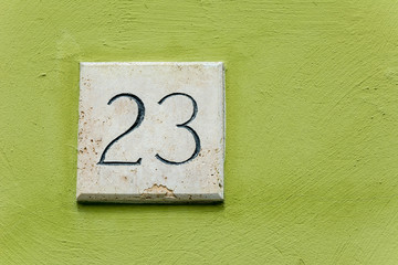 House number twent three on a stone plaque with a green wall bac