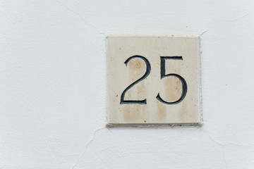 House number twent five on a stone plaque with a green wall back