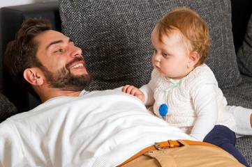 Vater und Kind zuhause auf dem Sofa