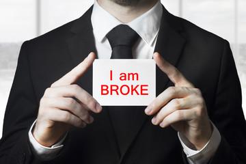 businessman holding sign i am broke