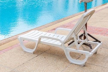 Beach chair near a blue swimming pool