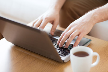 close up of man with laptop and cup at home