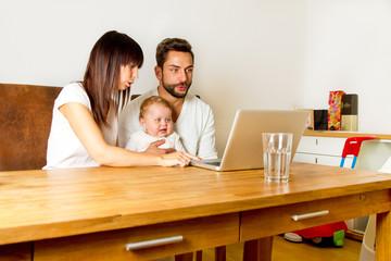 Junge Familie zuhause am Computer
