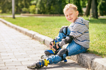 Little roller skater put on his skates